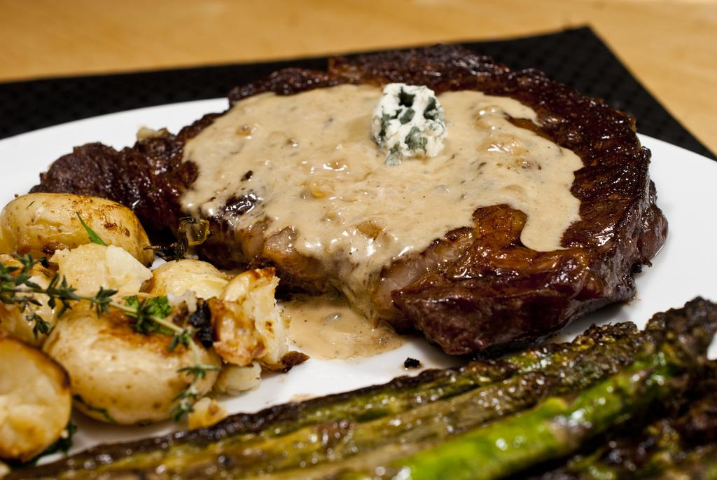 Steak with blue cheese sauce, herb smashed potatoes and grilled asparagus