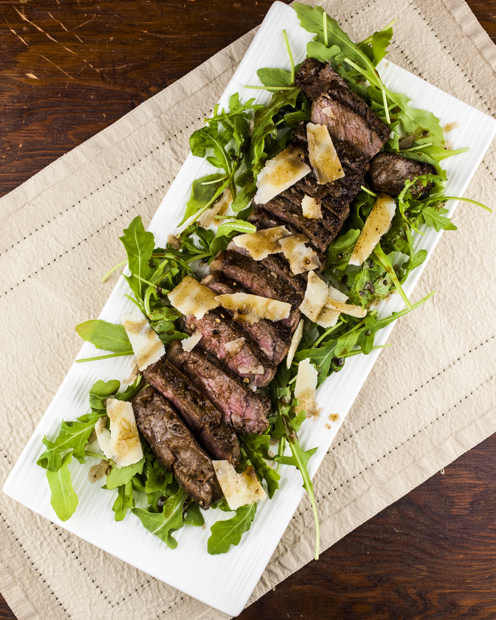 Tagliata on arugula with shaved parmesan and balsamic rosemary dressing